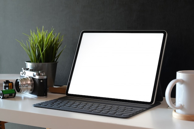 Mockup blank screen tablet on desk with vintage camera and creative supplies