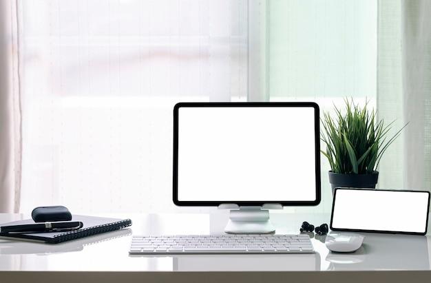 空白の画面タブレットをスタンドに、スマートフォンを白いテーブルにモックアップ