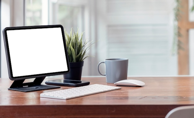 Планшет с пустым экраном макета на подставке, клавиатуре, мыши, смартфоне и кружке на деревянном столе с копией пространства.