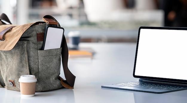 테이블과 어깨 가방에 빈 화면 스마트 폰에 모형 빈 화면 태블릿. 온라인 개념 작업.