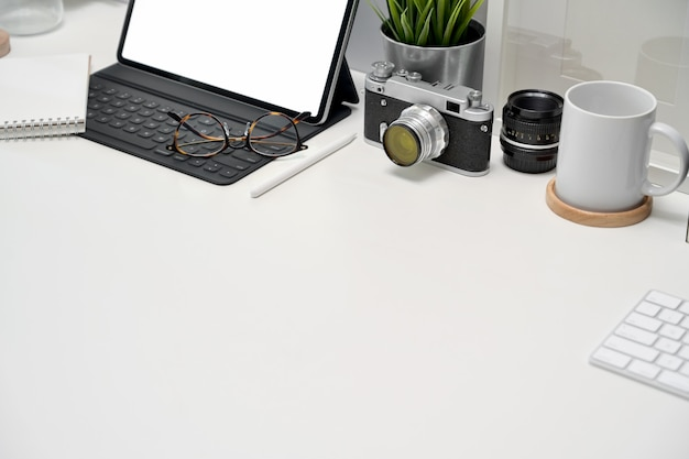 Mockup blank screen tablet, poster, books and vintage camera on workspace