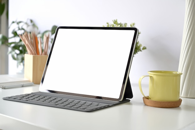 Mockup blank screen tablet and smart keyboard on white table