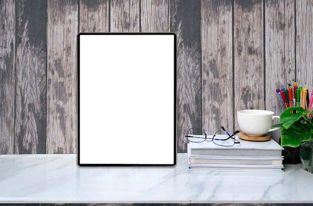 Mockup blank screen tablet and supplies on marble table with old wooden wall.