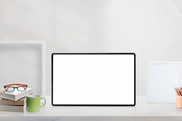 Mockup blank screen tablet on white wooden table  with supplies.
