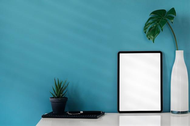 白いテーブルと青い壁の背景に装飾が施された空白の画面タブレットをモックアップします。快適なワークスペースのコンセプト。