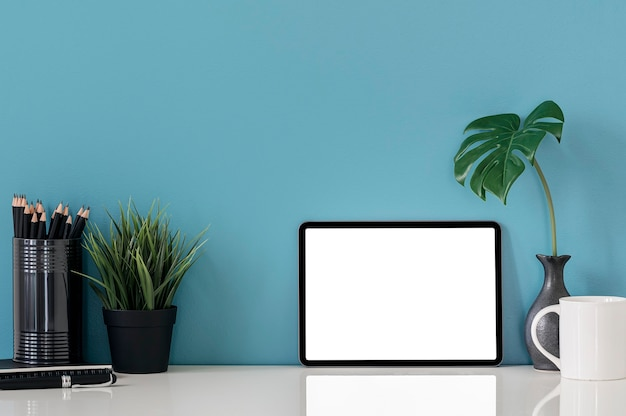 白いテーブルに装飾が施された空白の画面タブレットをモックアップします。快適なワークスペースのコンセプト。