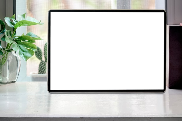 Mockup blank screen tablet with houseplant and book on white wooden table, blank screen for graphic design.