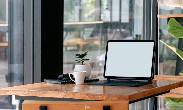リビングルームの木製テーブルにキーボードとコーヒーカップとモックアップ空白画面タブレット。