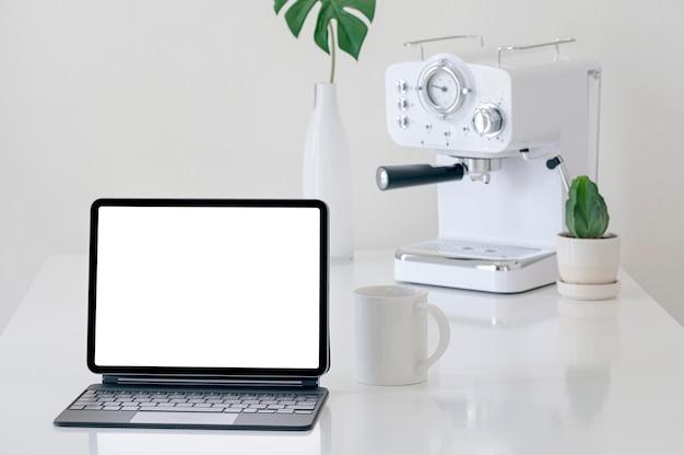 부엌 방에 흰색 테이블에 키보드, 찻잔 및 커피 기계와 모형 빈 화면 태블릿.