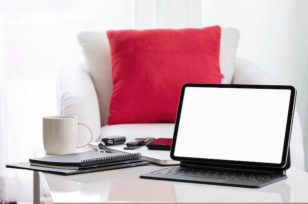 집에서 거실에 흰색 테이블에 키보드와 모형 빈 화면 태블릿.