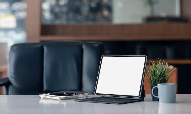 Планшет пустой экран макета с клавиатурой на белом столе в офисной комнате.