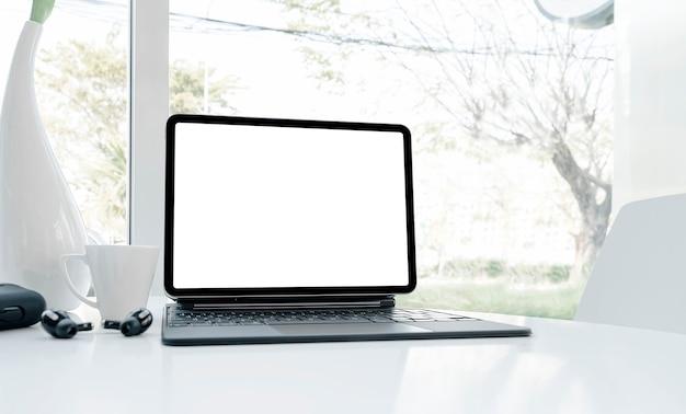 Таблетка пустого экрана макета с клавиатурой на белом столе в белой офисной комнате.