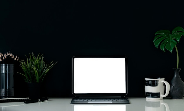 검은 배경에 흰색 테이블에 키보드와 모형 빈 화면 태블릿.