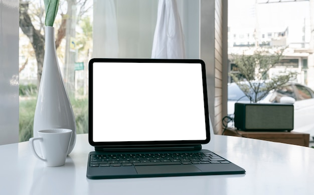 Таблетка пустого экрана макета с клавиатурой на белой таблице.