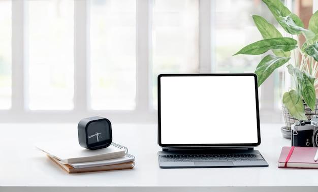 リビングルームの白いトップテーブルにキーボードとモックアップ空白画面タブレット