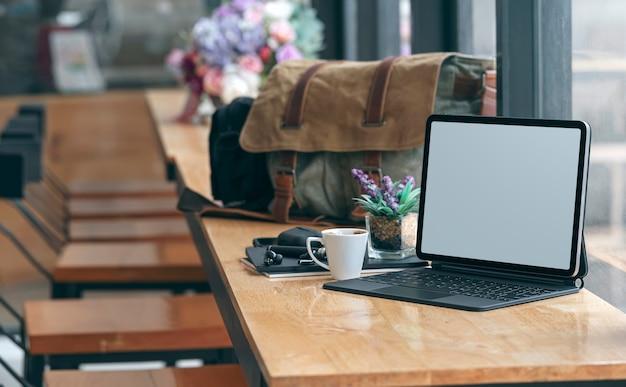 Таблетка пустого экрана макета с клавиатурой на деревянном счетчике в кафе.