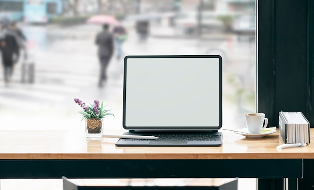 カフェの木製テーブルにキーボード付きのモックアップ空白画面タブレット。