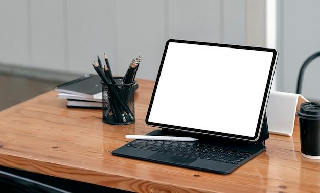 共同ワークスペースの木製テーブルにキーボード付きのモックアップ空白画面タブレット。
