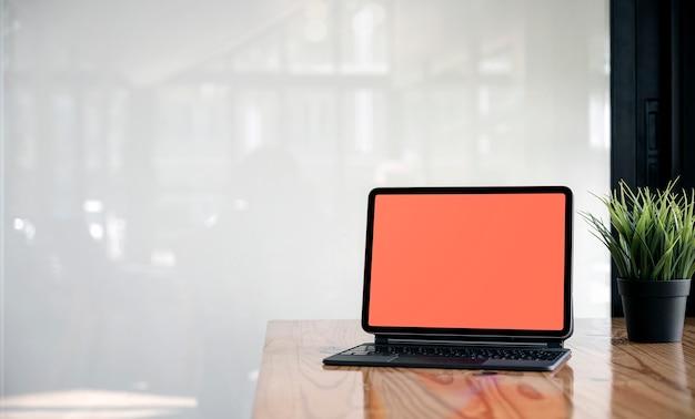 Таблетка пустого экрана макета с клавиатурой на деревянном столе в пустой комнате.