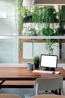 Таблетка пустого экрана макета с клавиатурой на деревянном столе в гостиной с зеленым фоном комнатных растений. вертикальный вид.
