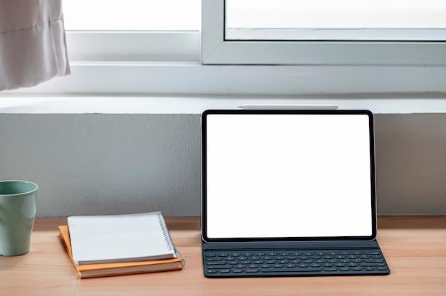 Планшет пустого экрана макета с клавиатурой на деревянном столе.