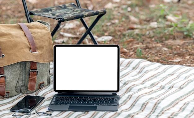 Планшет пустого экрана макета с клавиатурой, смартфоном, сумкой и стулом на коврике.
