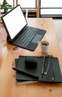 Планшет пустого экрана макета с волшебной клавиатурой и принадлежностями на деревянном столе в офисной комнате, вертикальный вид.