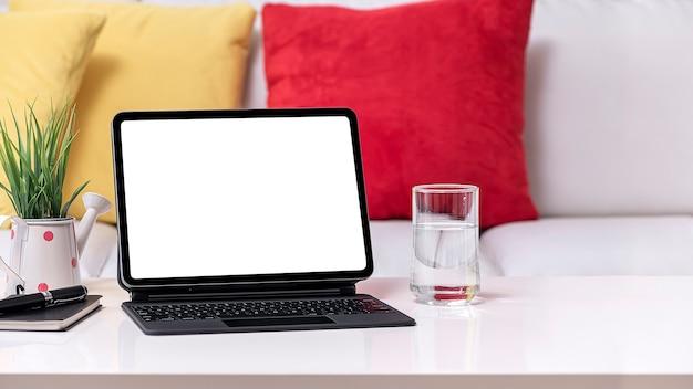Планшет пустой экран макета с волшебной клавиатурой на белом столе в гостиной.