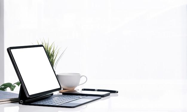 白いテーブルの白い明るい背景とコピースペースに魔法のキーボードとモックアップ空白画面タブレット。