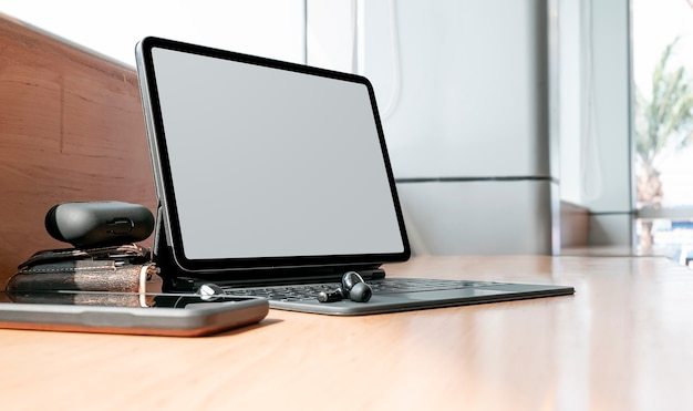 Таблетка пустого экрана макета с волшебной клавиатурой на деревянном счетчике.