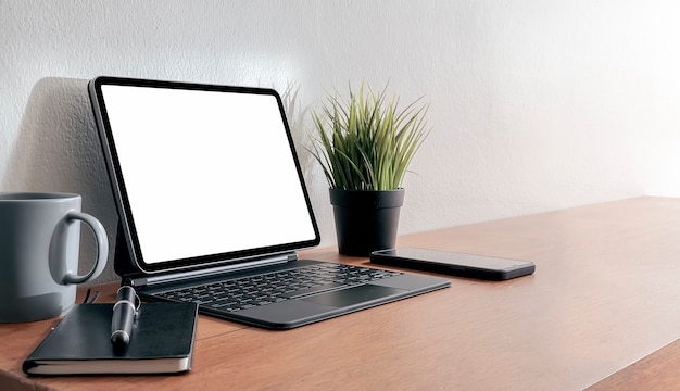 Макет планшета с пустым экраном с волшебной клавиатурой на деревянном столе