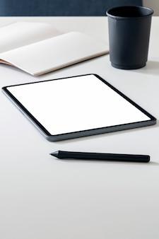 白いトップテーブル、垂直ビューにペンでモックアップ空白画面タブレット。