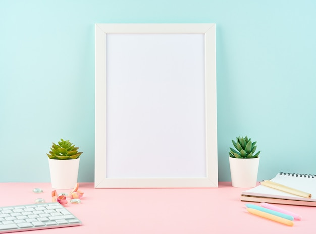 Mockup  blank white frame, alarm, notepad, keyboard on pink table against blue wall with copy. modern bright office desktop