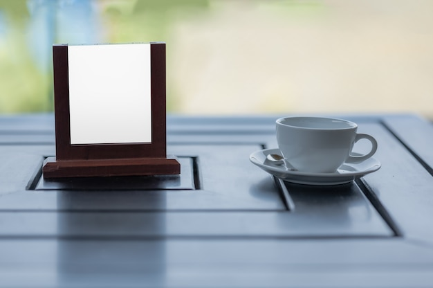 Mockup blank white screen advertising board with a coffee cup at a cofe table