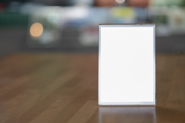 Mockup blank white screen advertising board on wooden table with blurred background