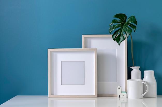 水色の壁と白いトップテーブルの上のモックアップ空白の木製額縁とセラミック花瓶。