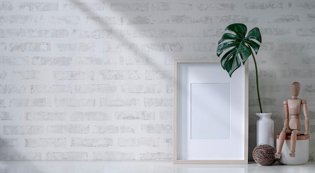 レンガの壁と白いテーブルの上のモックアップ空白の木製額縁。