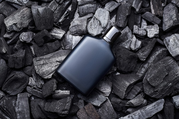 Mockup of blue fragrance perfume bottle mockup on dark coals background. top view. horizontal