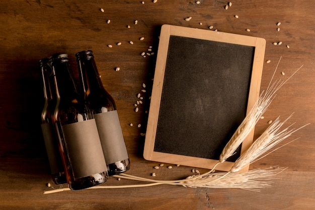 Mockup of brown bottles of beer with blackboard on wooden table
