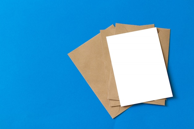Mockup brown kraft envelope document with blank white card isolated on blue background