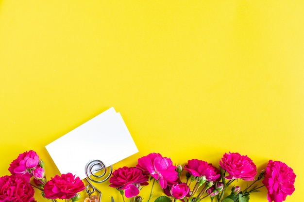 Mockup business cards on a colored background and a rose flower, copyspace, topview.