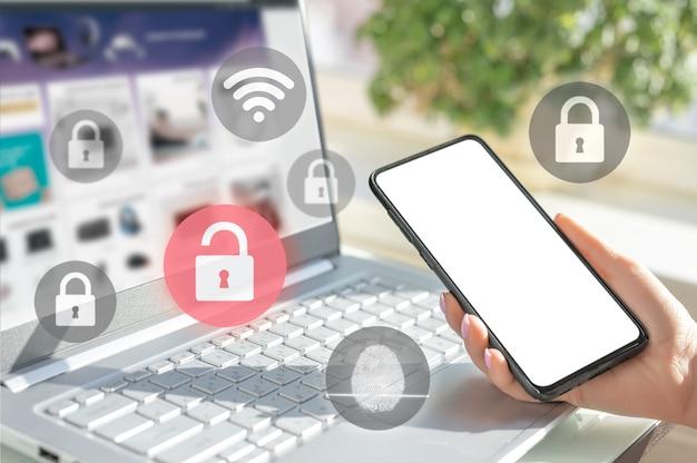 Мокап мобильного телефона. предприниматель держать сотовый телефон. женщина входит в ноутбук и держит смартфон под рукой со значком блокировки ключа безопасности на экране. концепция защиты конфиденциальности, интернета и мобильной безопасности