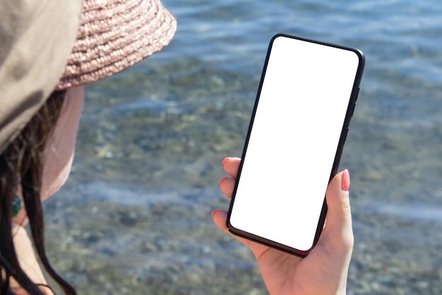 모형 핸드폰 바다 휴가. 손을 잡고 빈 흰색 휴대 전화 바다 배경을 보여주는 모형 이미지