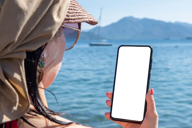 Мокап мобильного телефона на море. женщина рука мобильный телефон с пустой экран против морского пляжа открытый. роуминг в отпуске