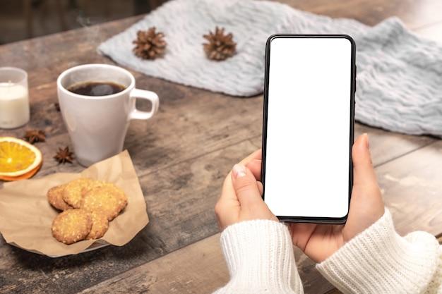 Мокап мобильного телефона. женщина в шерстяном свитере держит макет мобильного телефона,