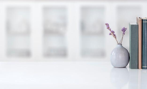 モダンな部屋の白い上のテーブルの上の本が付いている観葉植物のモックアップセラミック花瓶。スペースをコピーします。