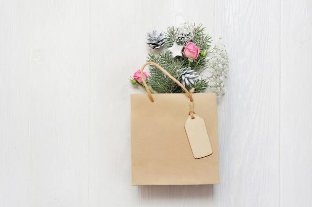 木と白の花で飾られたモックアップクリスマスギフトパック