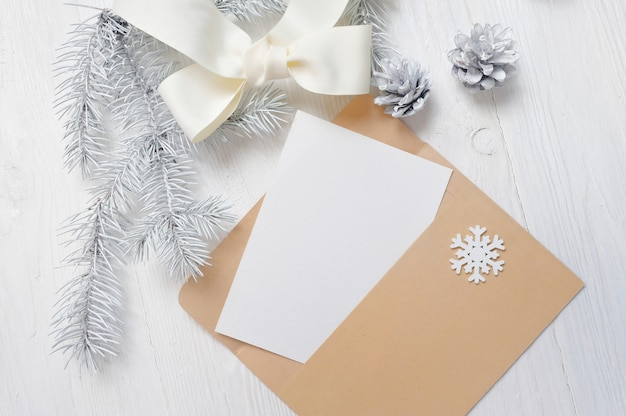 Mockup christmas greeting card letter in envelope with white tree and cone