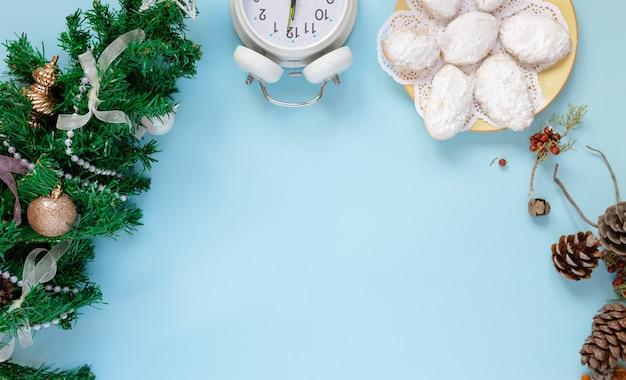 モックアップクリスマスグリーティングカードの上面図と新年のツリー、モミの円錐形、時計、クッキー、真ん中の白いシートにあなたのテキストのための場所を青の背景にフラットレイ。