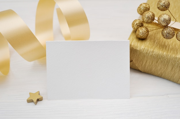 Mockup christmas greeting card with gold gift ribbon, flatlay on a white wooden background Premium Photo